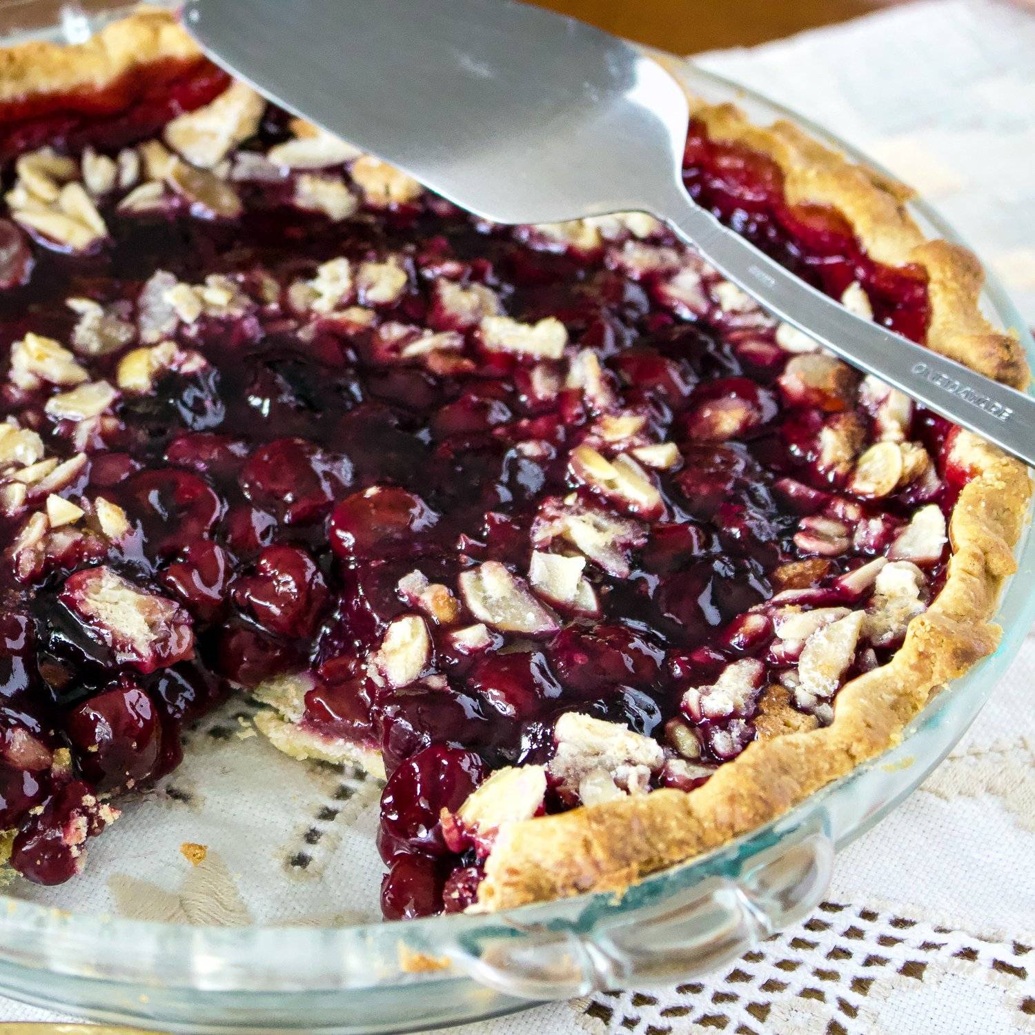 Best Sour Cherry Pie- in the glass baking pan with a serving spoon