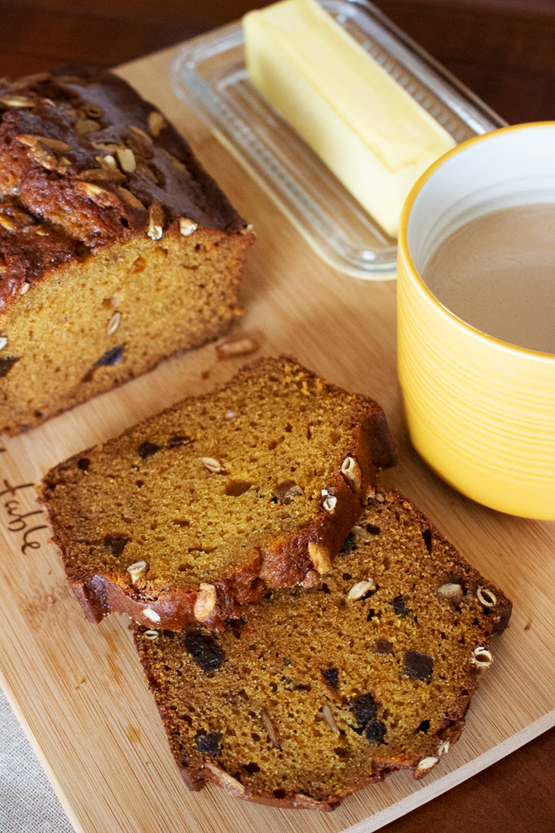 Pumpkin Seed And Apricot pumpkin Sweet Bread-slices of bread on a wood board with butter and a yellow cup of coffee