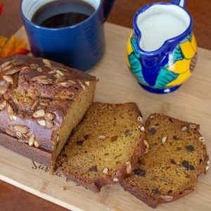 Pumpkin Seed And Apricot Pumpkin Sweet Bread sliced with blue coffee mug and milk