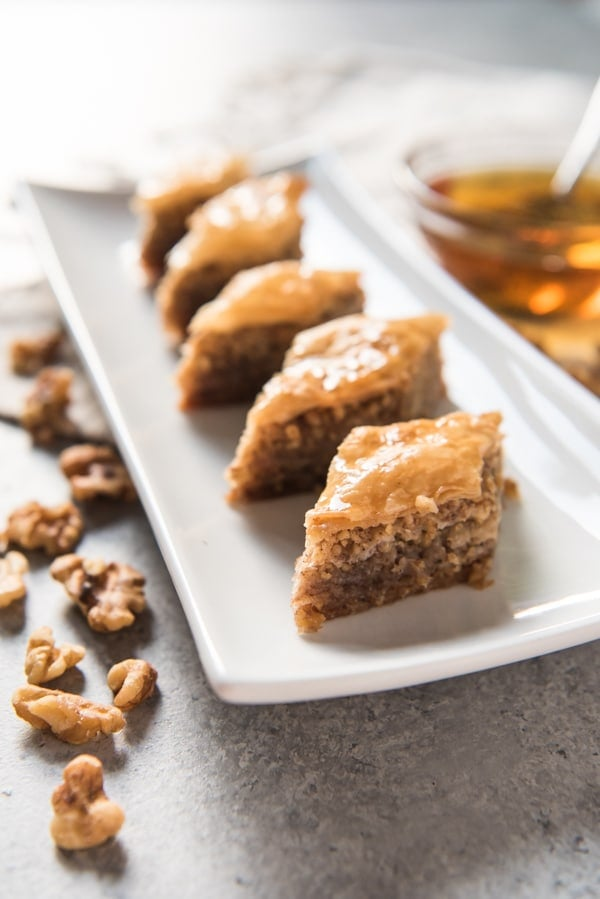Slices of honey walnut Greek baklava arranged on a white plate surrounded by walnuts and honey.