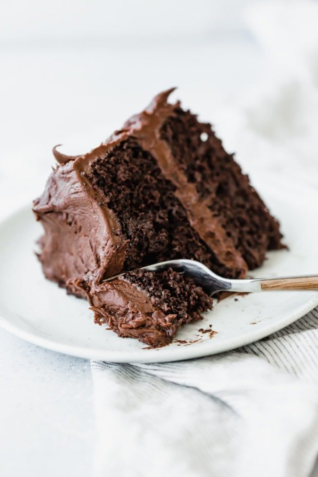 A fork cutting into a piece of double layered chocolate cake.