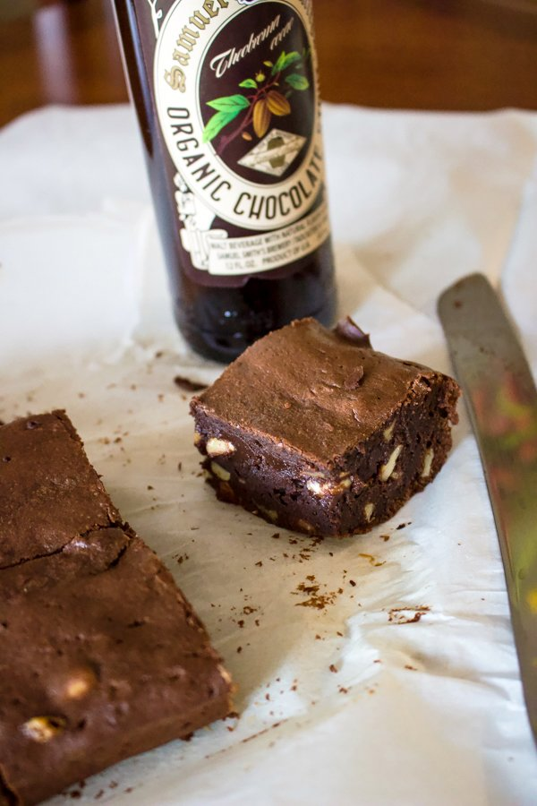brownies on the table with a bottle of stout in the background