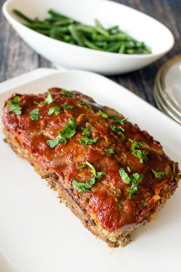 Old Fashioned Meatloaf With Oats Midwest Style-on a white plate next to cooked green beans
