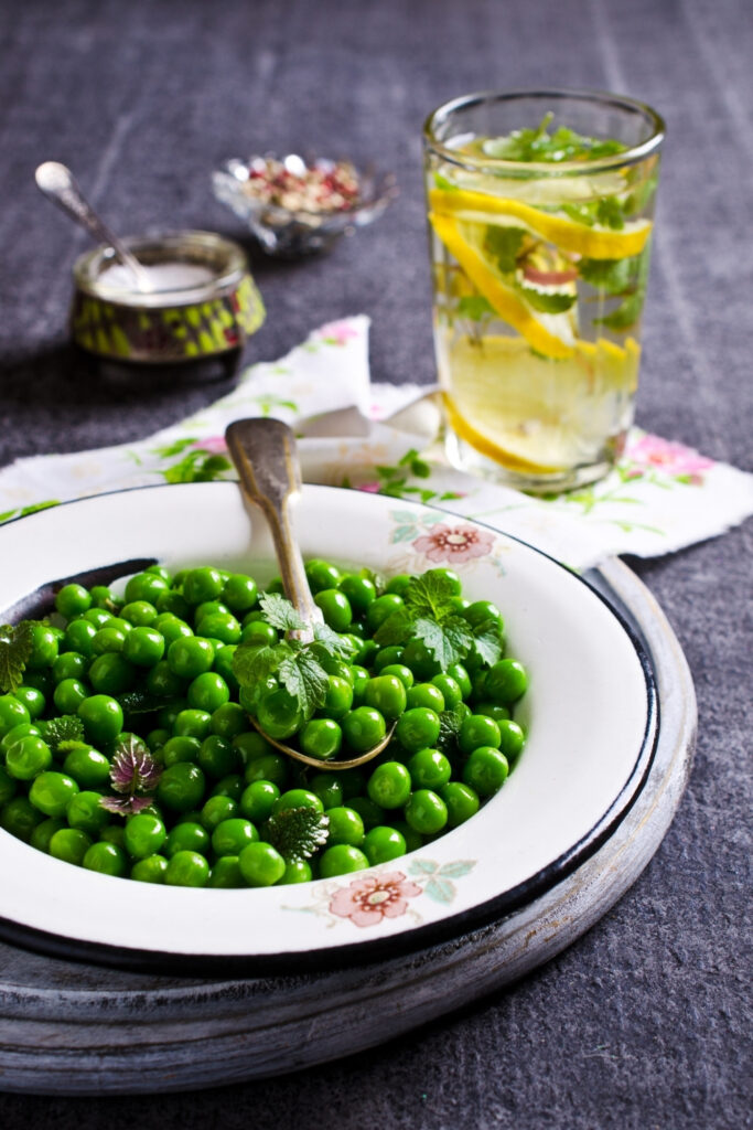 Super Easy Green Peas With Mint in a white plate with spoon