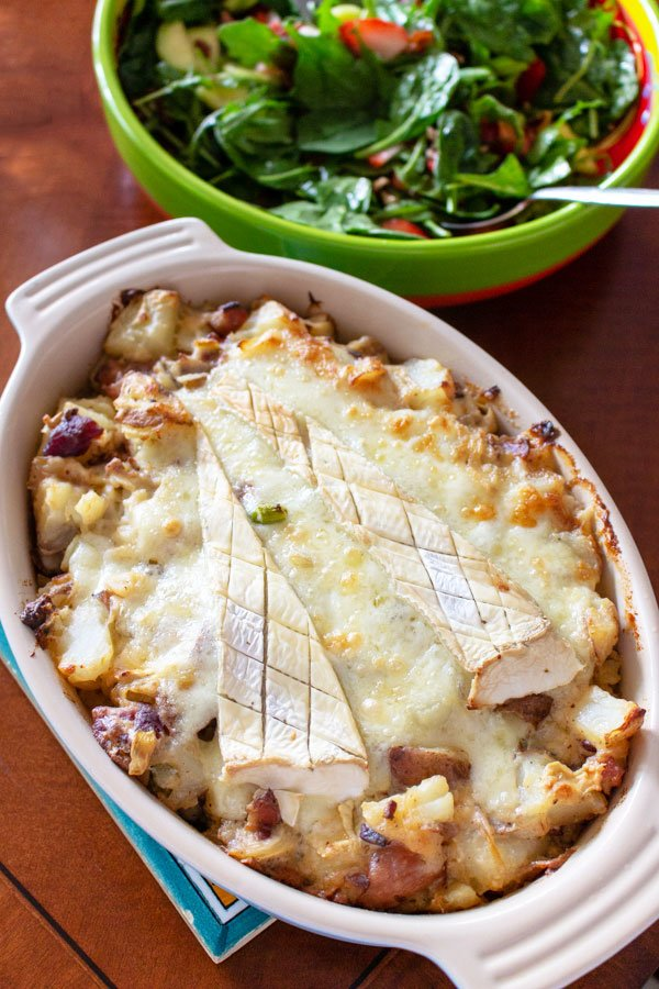 French Tartiflette- American version- close up- baked dish with salad in the background