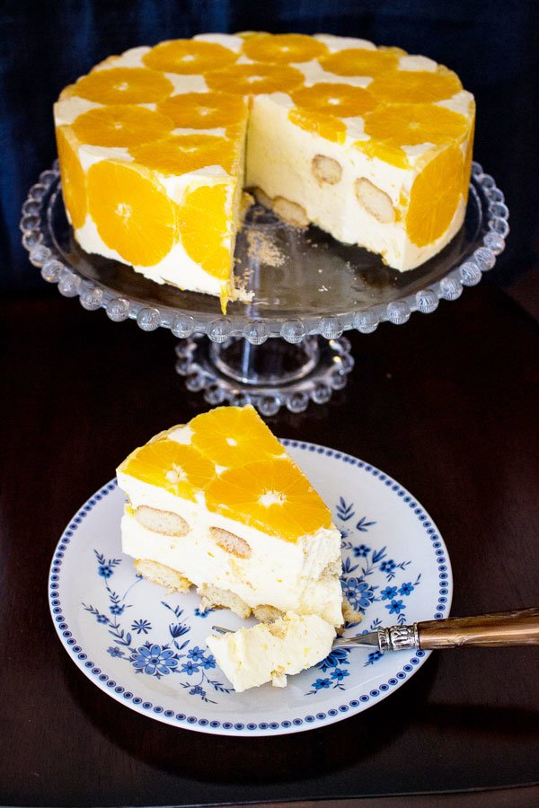 No Bake Orange Mousse Cake sliced on a white and blue plate with the cake on a cake stand in the background