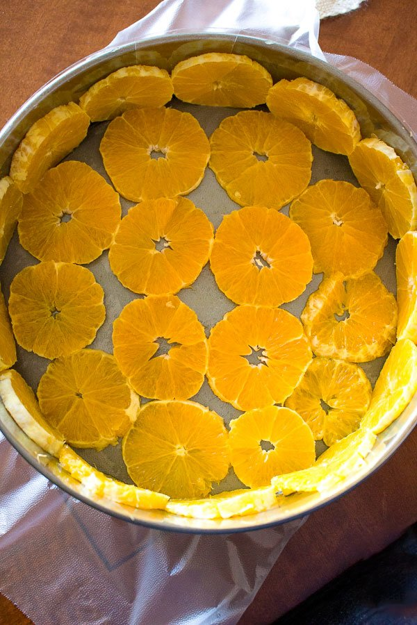 No Bake Orange Mousse Cake- first layer of sliced oranges in a cake pan
