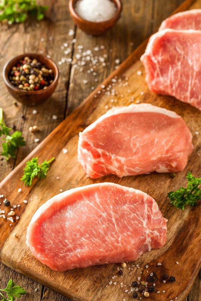 Boneless Pork Chops Raw on a cutting board