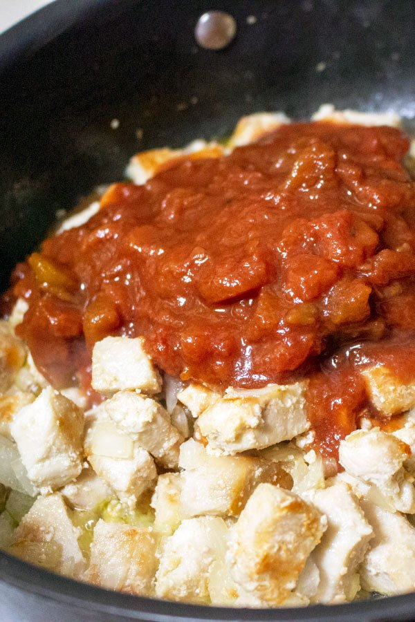 chicken breast, onions and tomatoes cooking in a pan
