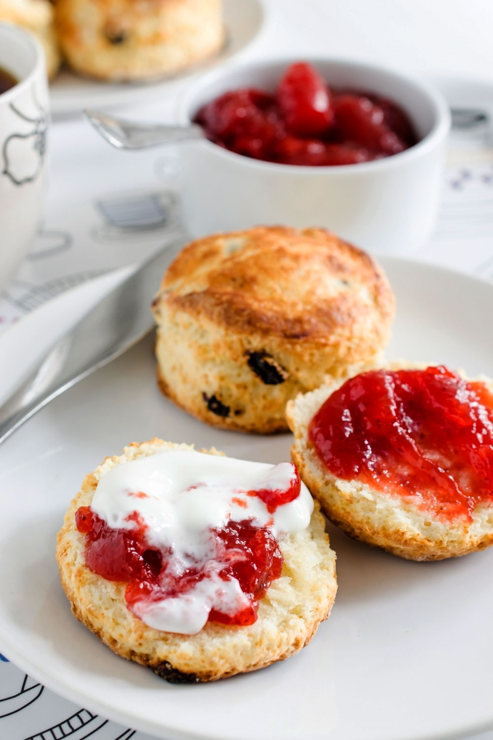 sliced scones with jam and cream