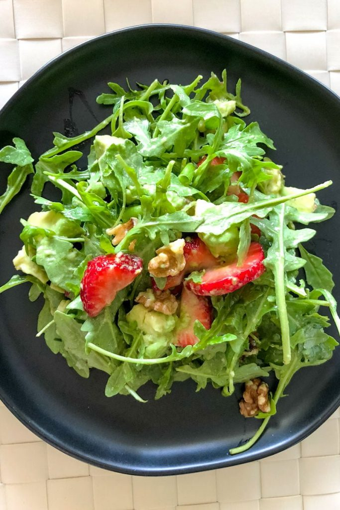 Strawberry Arugula Salad With Pecans And Avocado on a black plate