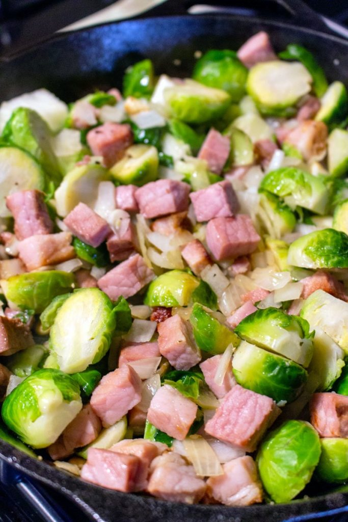 Brussel Sprouts and Ham cooking in a cast iron skillet