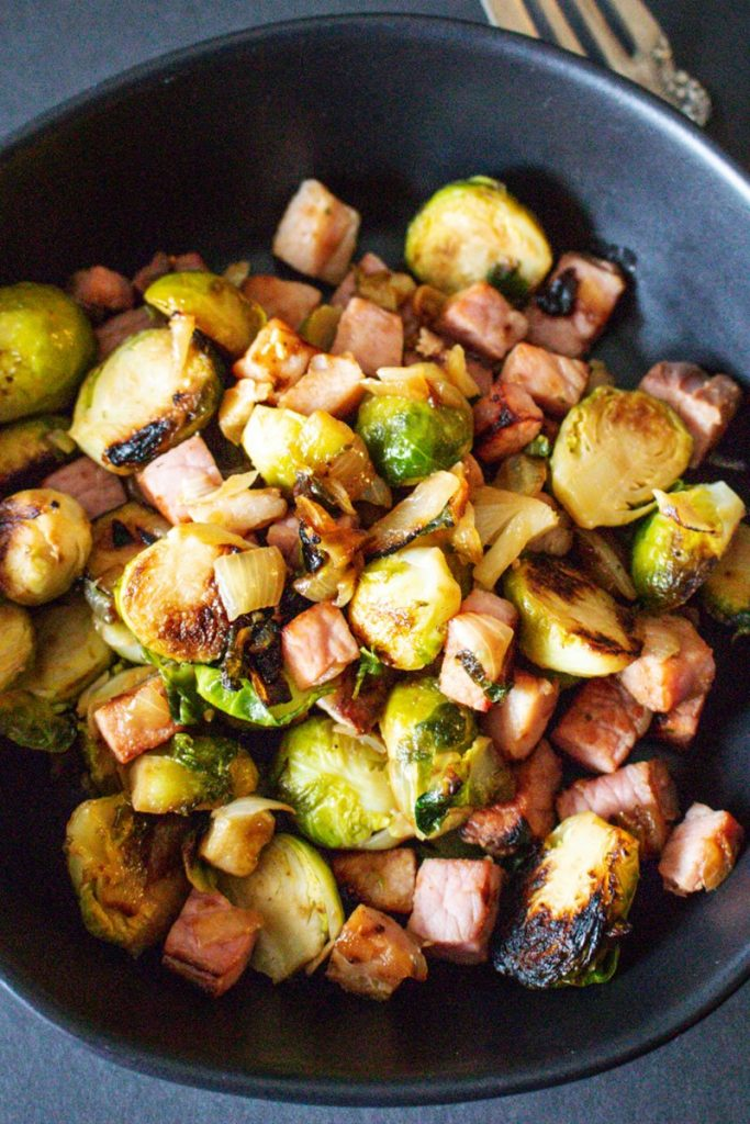 Brussel Sprouts with ham on a black plate