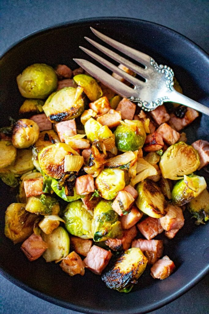 Brussels Sprouts with Ham on a dark plate with a fork