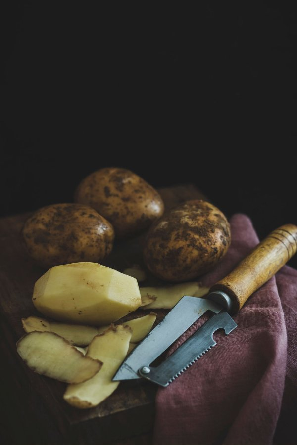 potatoes on a kitchen towel with knive