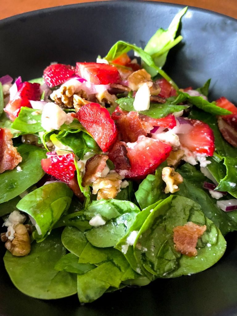 Spinach Strawberry Salad With Walnuts And Feta on a black salad bowl