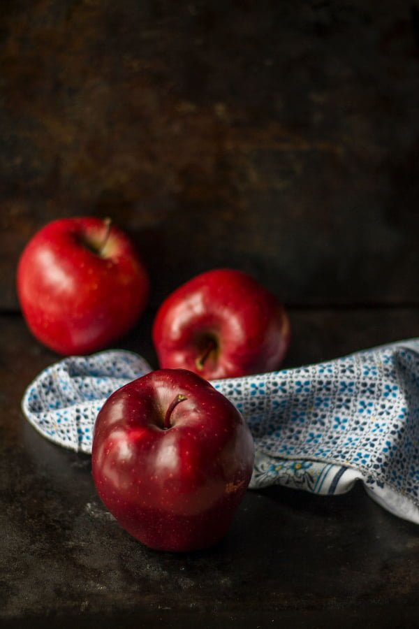 Apples on a dark table with kitchen towel