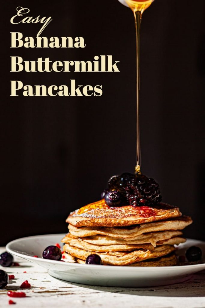 featured picture for Pinterest- pancakes on a white plate decorated with fresh blueberries and honey
