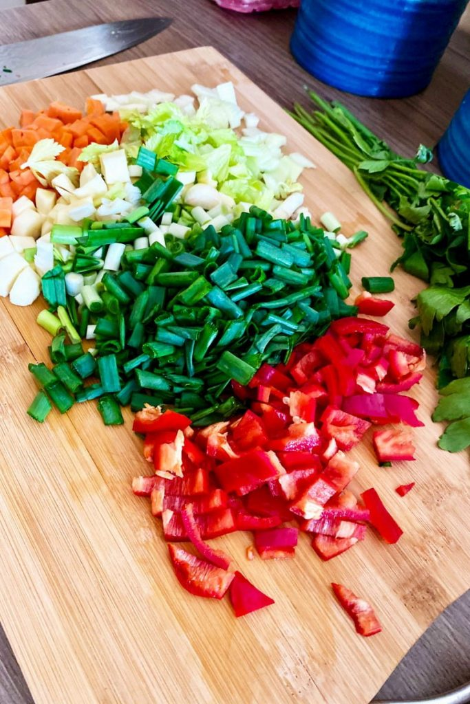 Instant Pot Beef Vegetable Soup- cutting board with chopped carrots, onions, peppers and celery