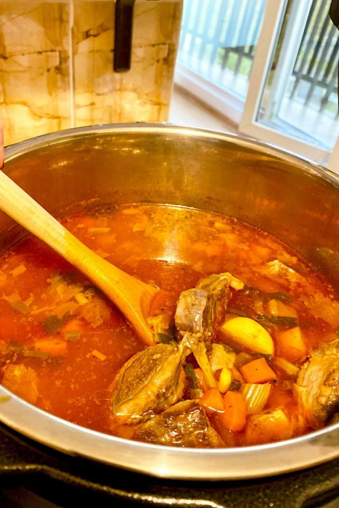 Instant Pot Beef Vegetable Soup- picture of the soup in the pot and wooden spoon