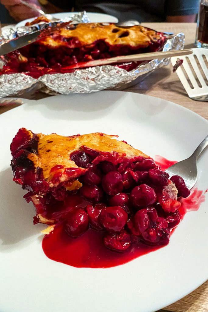 slice of cherry pie on a white plate with fork