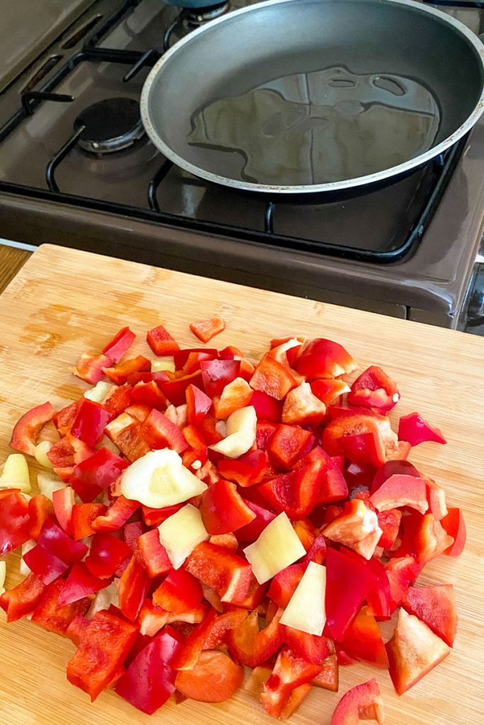 Fried peppers with tomatoes eggs and cheese- chopping the peppers