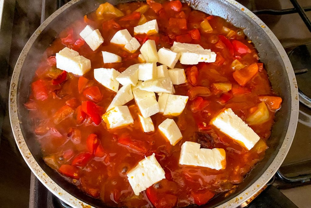 Fried peppers with tomatoes eggs and cheese- as part of the cooking process: adding the Feta cheese