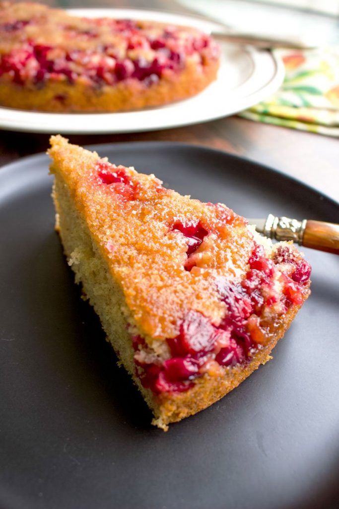 cranberry upside down cake -slice of cake on black plate with fork