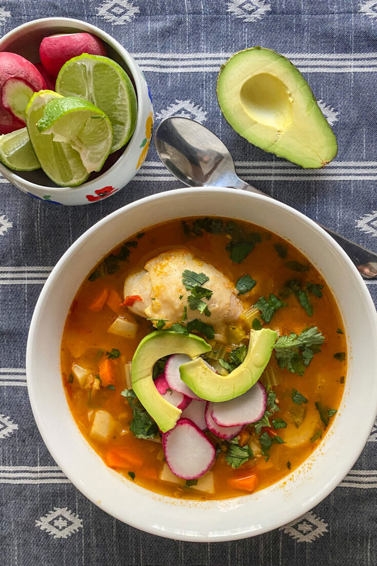 caldo de pollo served on white bowl with avocado (Caldo de Pollo Or Chicken Soup Mexican Style)
