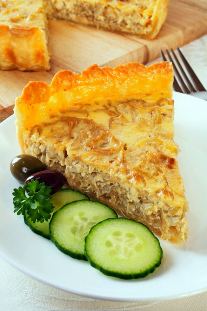 Caramelized onion tart slice on plate with cucumbers and olives0