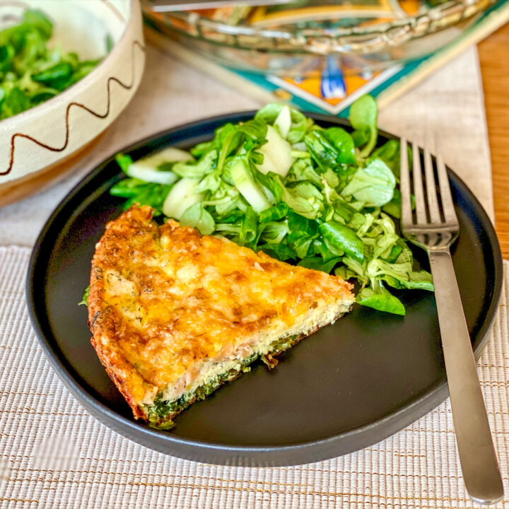Salmon and Spinach Quiche slice on plate with greens square photo0