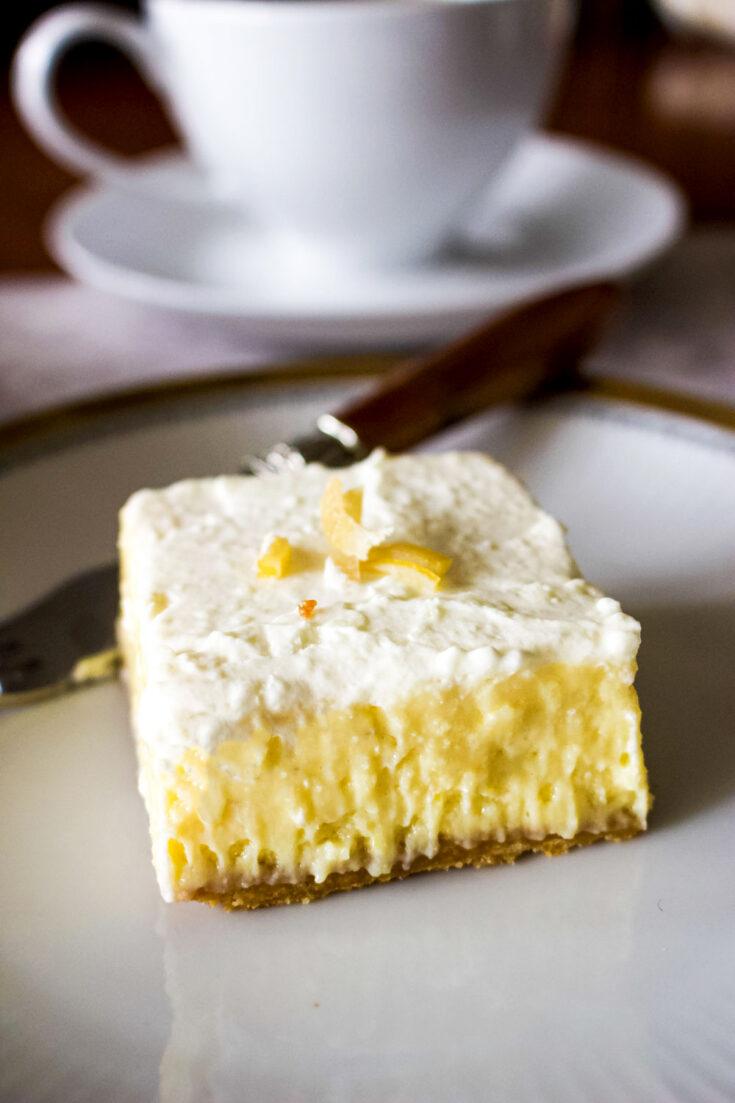 Slice of lemon bar on white plate with fork0