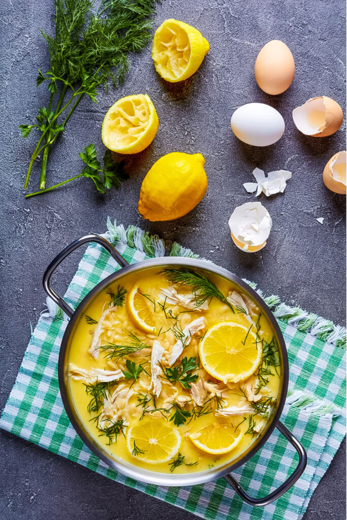 Greek Lemon Chicken Soup with lemons and eggs on table0