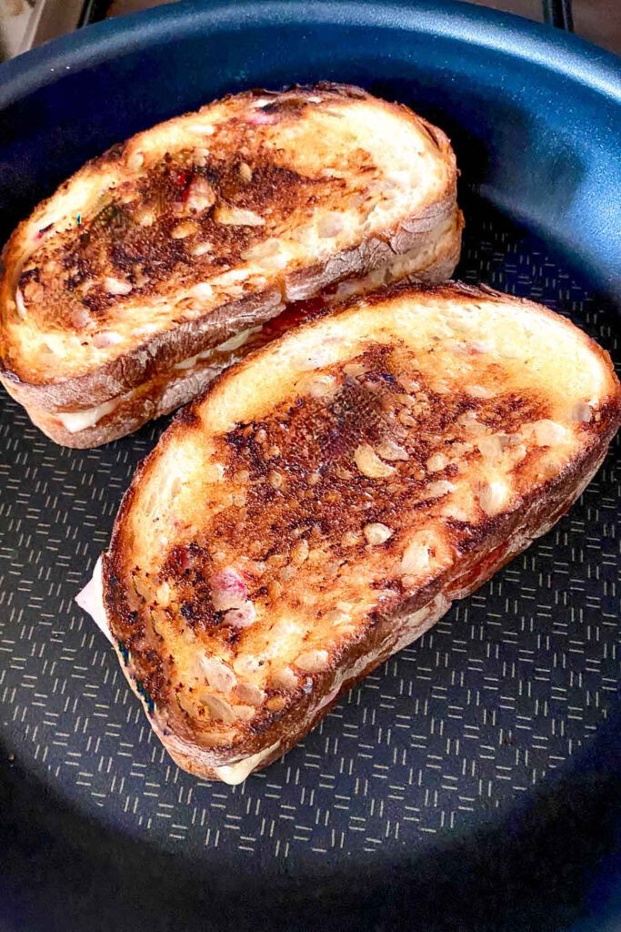 Ham and cheese sandwich in a pan grilled on one side0