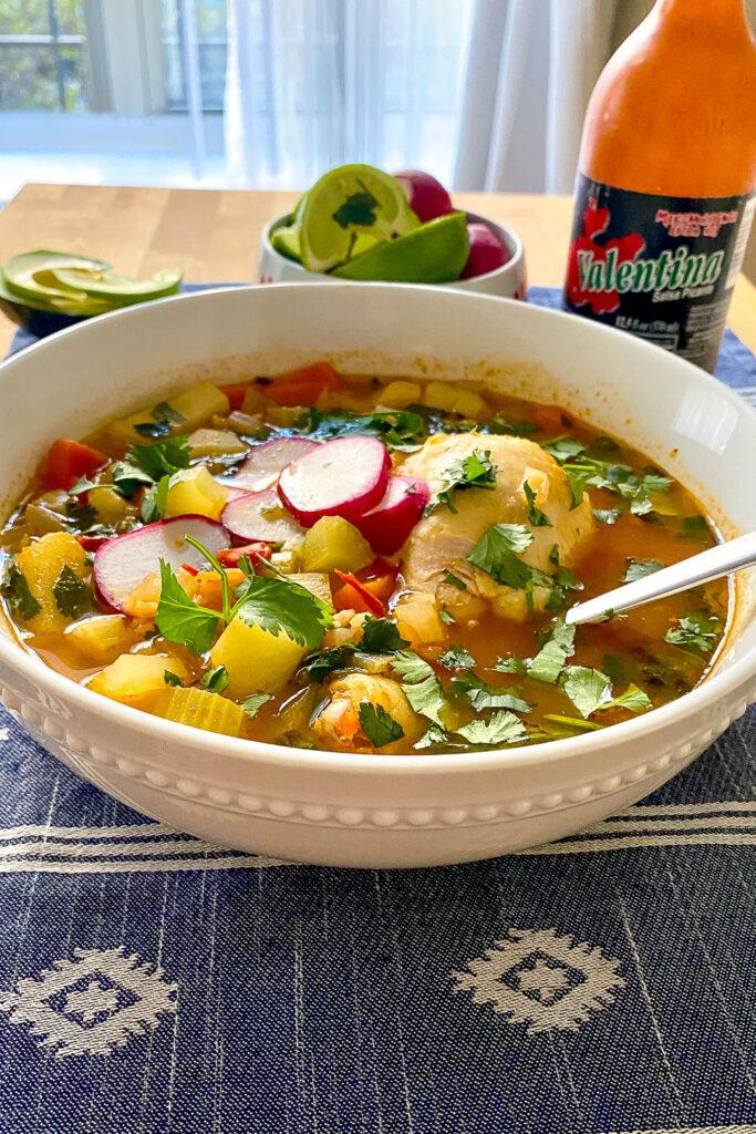 Caldo de Pollo Mexican Chicken Soup on table with salsa Valentina in the background0